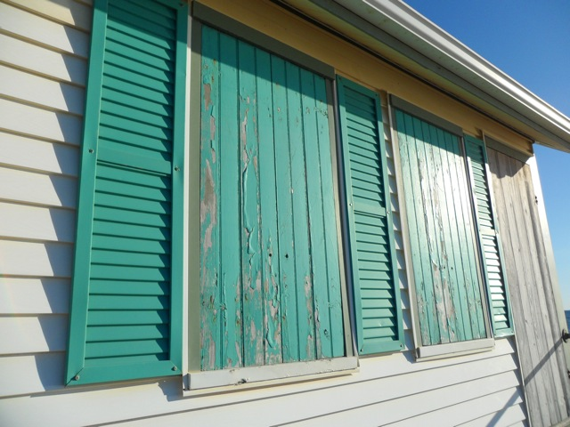 shuttered windows and boarded door